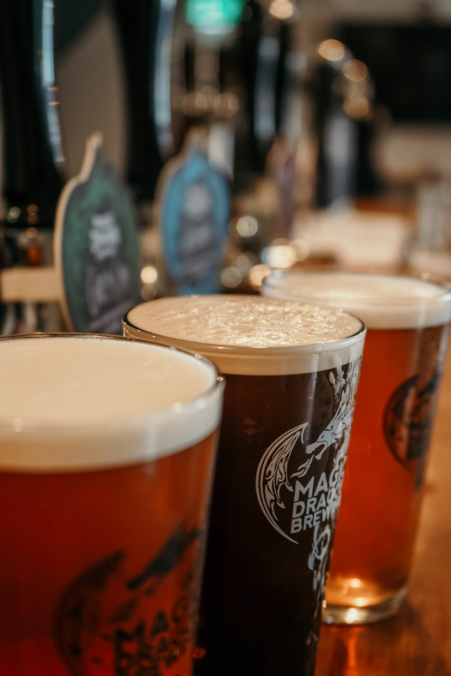 https://magicdragonbrewing.com/wp-content/uploads/2021/07/line-up-of-pints-scaled.jpg